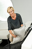 Woman arranging cushions on a couch and smiling