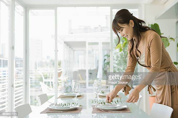 Woman arranging dinner table