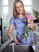 Woman Arranging Floral Decoration in Kitchen