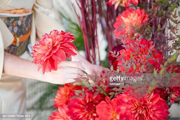 Woman arranging flowers, close up of hand