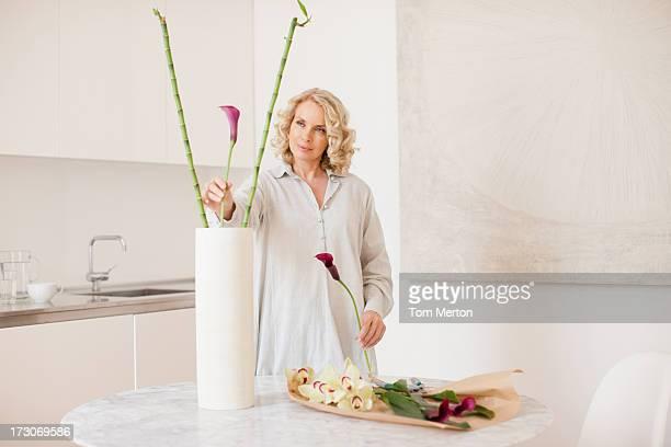 Woman arranging flowers in vase