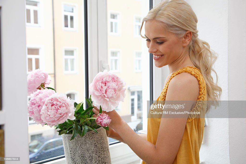 Woman arranging flowers in window : Stock Photo