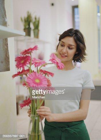 Woman arranging gerberas in vase, smiling : Stock Photo