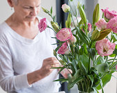 Older woman arranging pink lisianthus flowers with greenery in vase (selective focus)