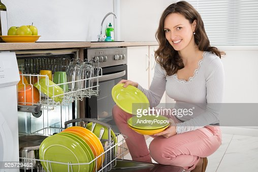 Woman Arranging Plates In Dishwasher : Stock Photo