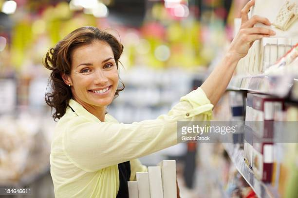 Woman arranging products on shelf