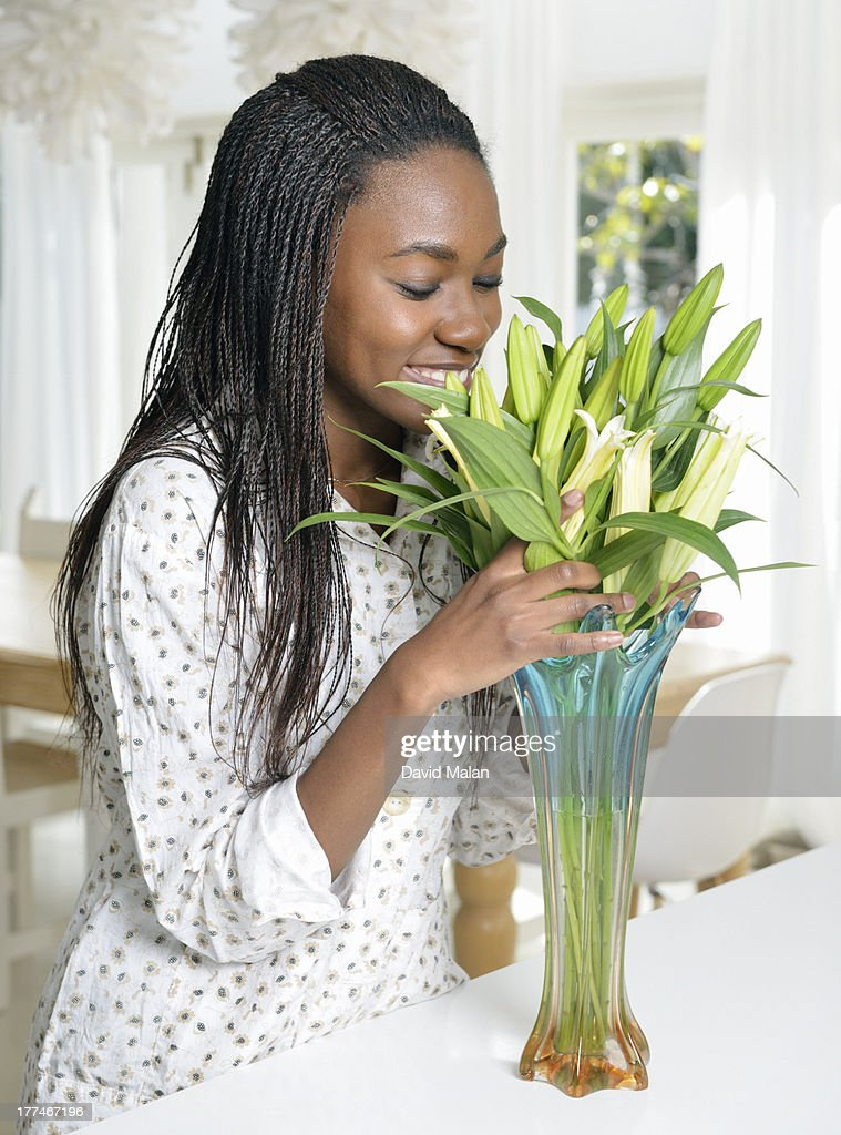 A woman arranging & smelling cut flowers : Stock Photo