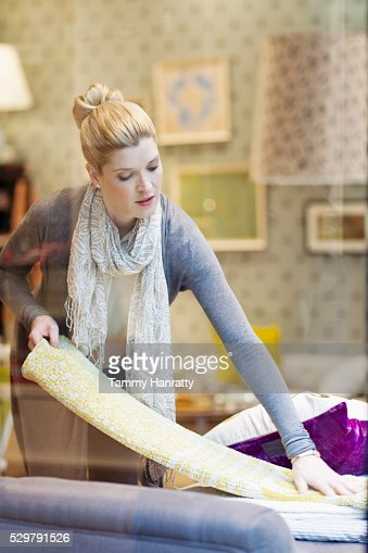 Woman arranging textile in shop : Stock Photo