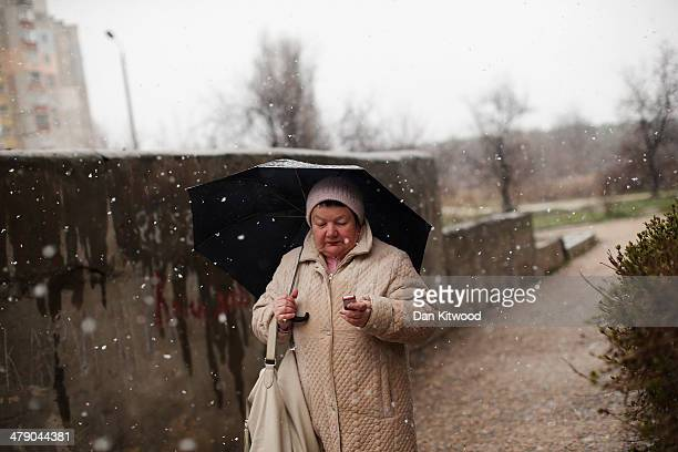 A woman arrives at a polling stationin the snowl on March 16 2014 in Simferopol Ukraine Crimeans go to the polls today in a vote that which will...