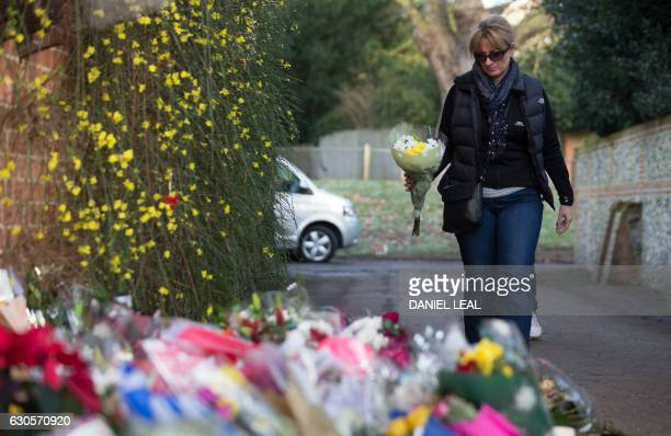 A woman arrives bearing flowers to add to the tributes piled outside the home of British singer George Michael where the singer died on Christmas Day...