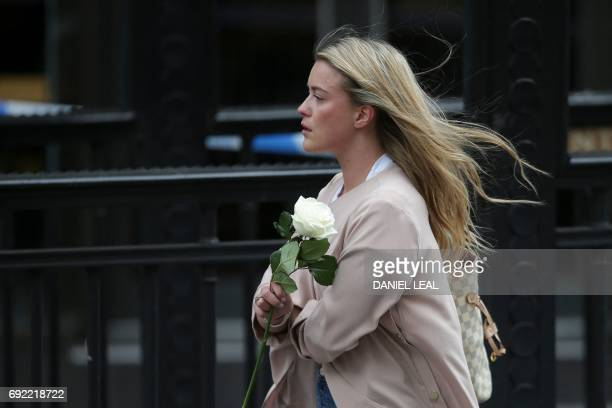 A woman arrives holding a single rose to lay at the police corden at the north end of London Bridge in London on June 4 in tribute to the victims of...