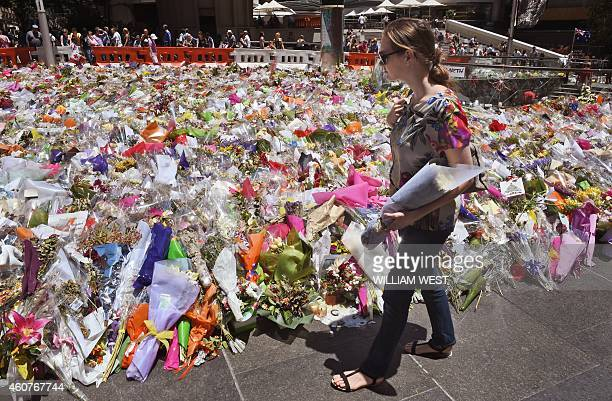 A woman arrives with a bouquet of flowers to add to the floral tributes left in Sydney's Martin place one week after a siege at the Lindt cafe which...