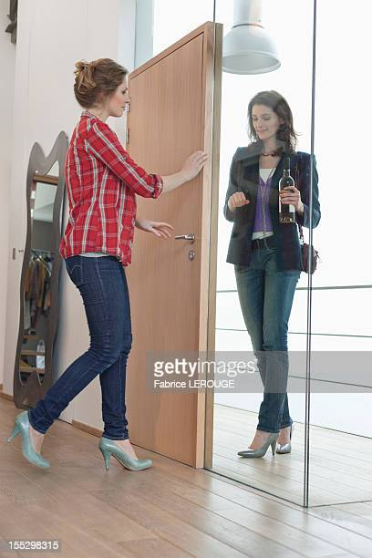 Woman arriving at her friends home with a wine bottle