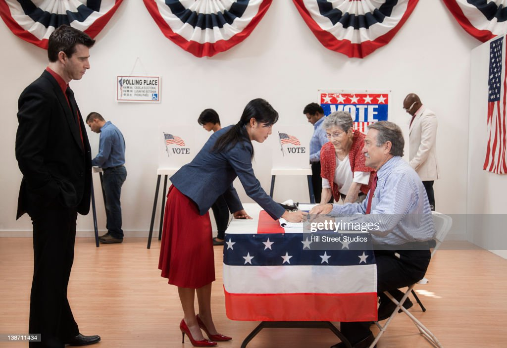 Woman arriving at registration desk in polling place
