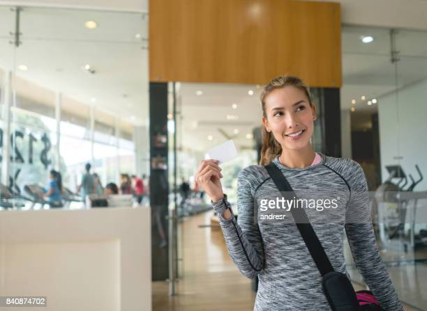 Woman arriving at the gym and holding a loyalty card