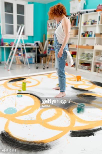 woman artist painting on the floor