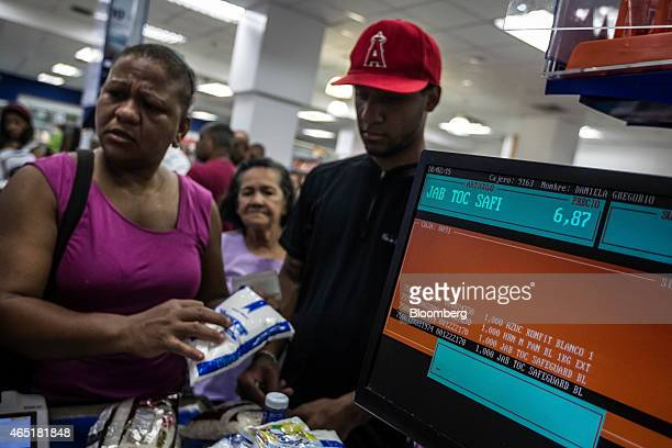 A woman asks a cashier about the price of an item at a privatesector grocery store in Caracas Venezuela on Wednesday Feb 18 2015 In Venezuela which...