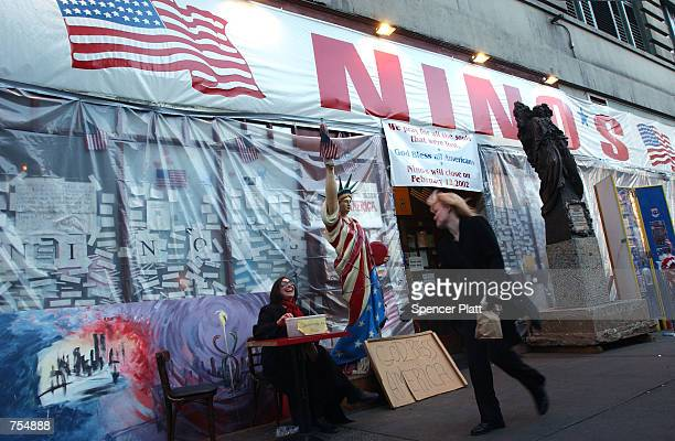 A woman asks a passerby for donations to a fund for September 11 victims in front of Nino's restaurant February 8 2002 in New York City Within 24...