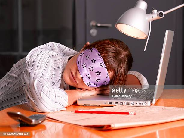Woman asleep at laptop wearing sleeping mask