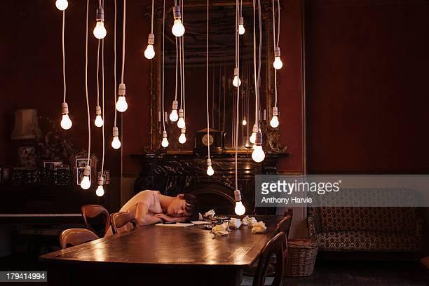 Woman asleep at table with hanging lightbulbs