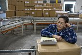 Woman asleep in distribution warehouse