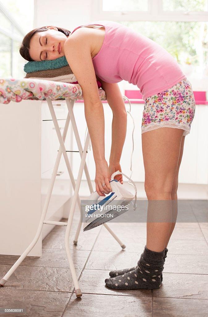 Woman asleep on ironing board