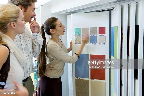 Woman assisting couple choosing color samples in store