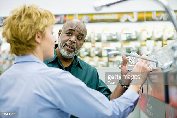Woman Assisting Customer in Hardware Store