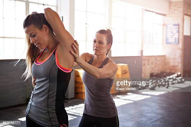 Woman assisting friend with stretch after training