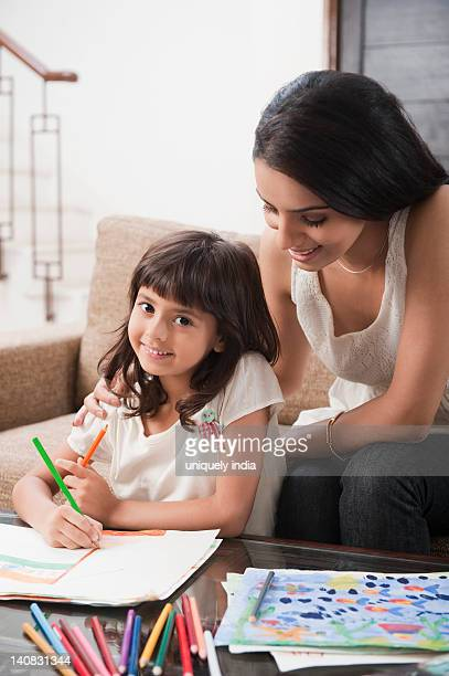 Woman assisting her daughter in drawing