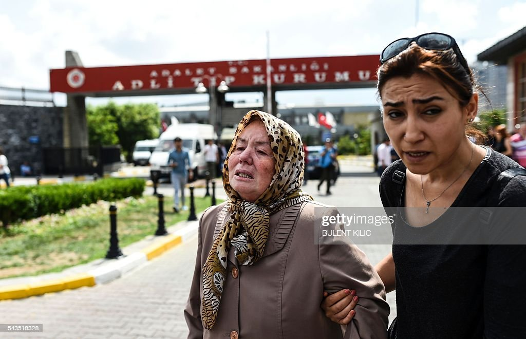 A woman assists a mother (C) who lost a relative, outside a forensic medicine building close to Istanbul's airport on June 29, 2016, a day after a suicide bombing and gun attack targeted Istanbul's airport, killing at least 36 people. A triple suicide bombing and gun attack that occurred on June 28, 2016 at Istanbul's Ataturk airport has killed at least 36 people, including foreigners, with Turkey's prime minister saying early signs pointed to an assault by the Islamic State group. / AFP / BULENT