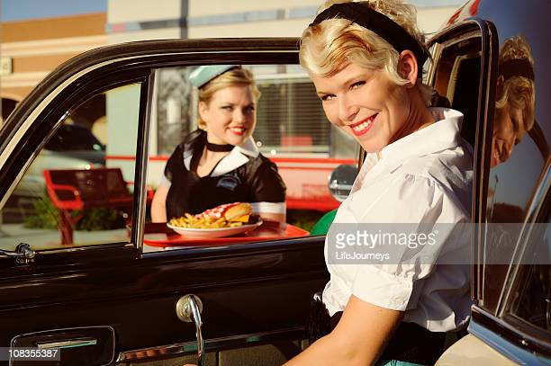 Woman At 50's Drive In Being Served By Car Hop