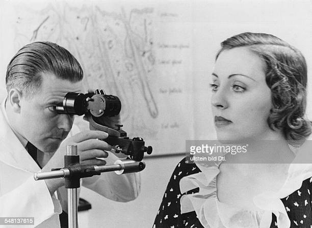Woman at a beauty parlor has her skin looked at and evaluated through a magnifying glass 1937 Published by 'Koralle' 7/1937 Vintage property of...