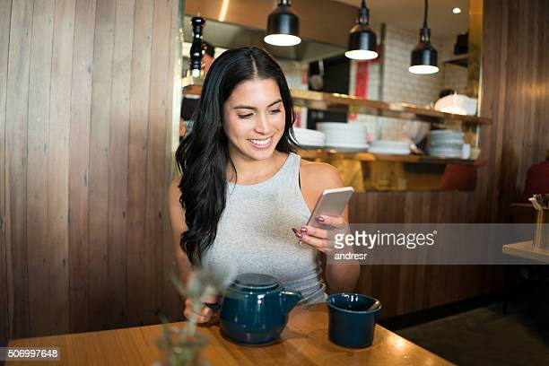 Woman at a cafe text messaging