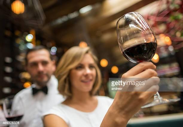 Mujer en una cava retención de una copa de vino