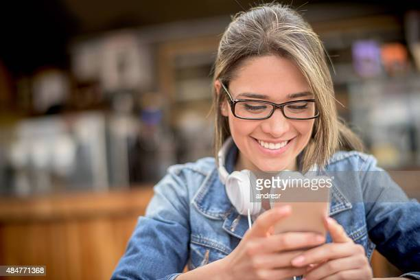 Woman at a coffee shop texting on her phone