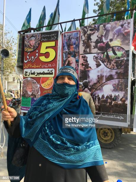 A woman at a Kashmir solidarity day rally from religious party holds banner in front of truck showing scenes of violence and death in Indian portion...