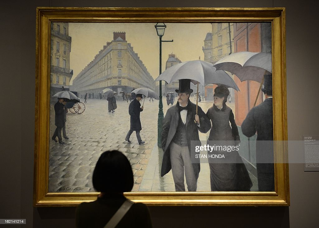 A woman at a media preview looks at 'Paris Street; Rainy Day, 1877' by Gustave Caillebotte in the exhibition 'Impressionism, Fashion, and Modernity' February 19, 2013 at The Metropolitan Museum of Art in New York. The look at the role of fashion in the works of the Impressionists and their contemporaries shows 80 major paintings with period costumes, accessories, fashion plates, photographs, and popular prints. AFP PHOTO/Stan HONDA