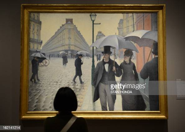 A woman at a media preview looks at 'Paris Street Rainy Day 1877' by Gustave Caillebotte in the exhibition 'Impressionism Fashion and Modernity'...