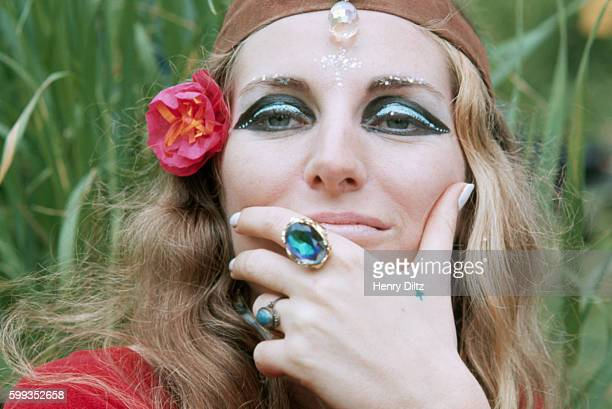A woman at a sitin wears typical hippie attire including crystal jewelry and scarf around her head She is also wearing heavy eyeshadow