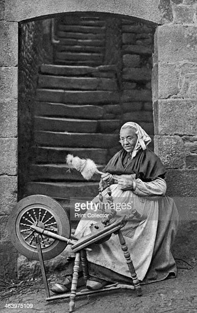 A woman at a spinning wheel Dinan Brittany France c1922 A print from Peoples of all Nations Volume III edited by JA Hammerton The Fleetway House...