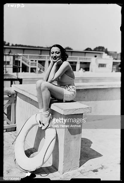 Woman at a swimming baths 1934 A photograph of a young woman sitting on a wall at Farnboro outdoor swimming pool taken by James Jarche for the Daily...