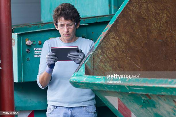 Woman at a waste container looking at digital tablet