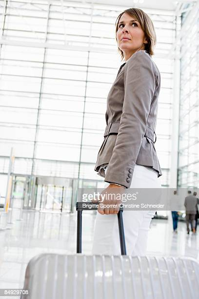 Woman at airport dragging suitcase