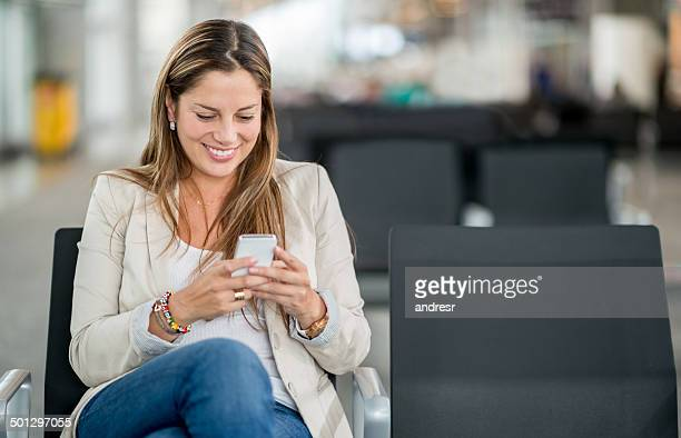 Woman at airport texting on a smartphone