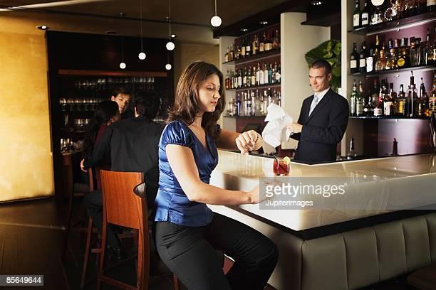 Woman at bar looking at watch