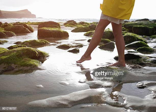 Woman at beach dipping toe in rock pool