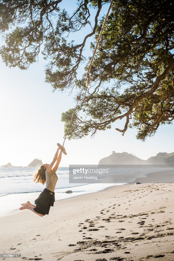 Woman at beach having fun on rope swing