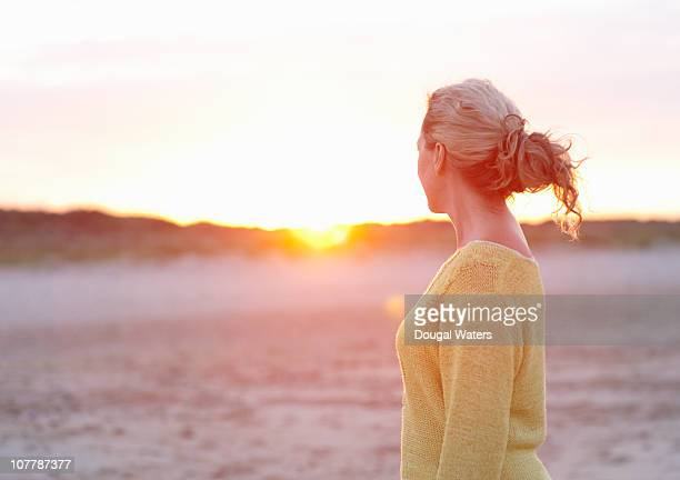 Woman at beach watching sunset.