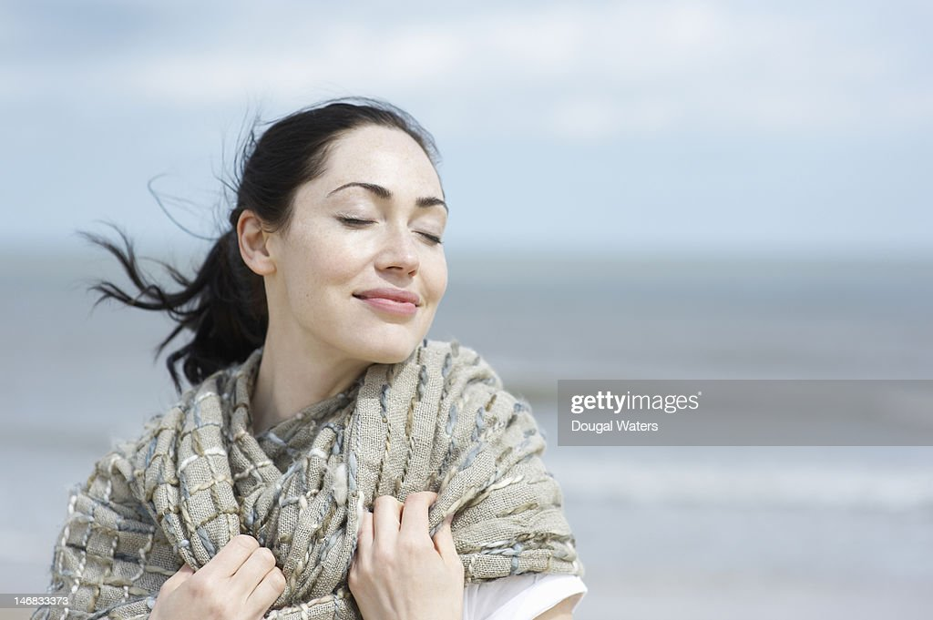Woman at beach with eyes closed and smiling. : Stock Photo